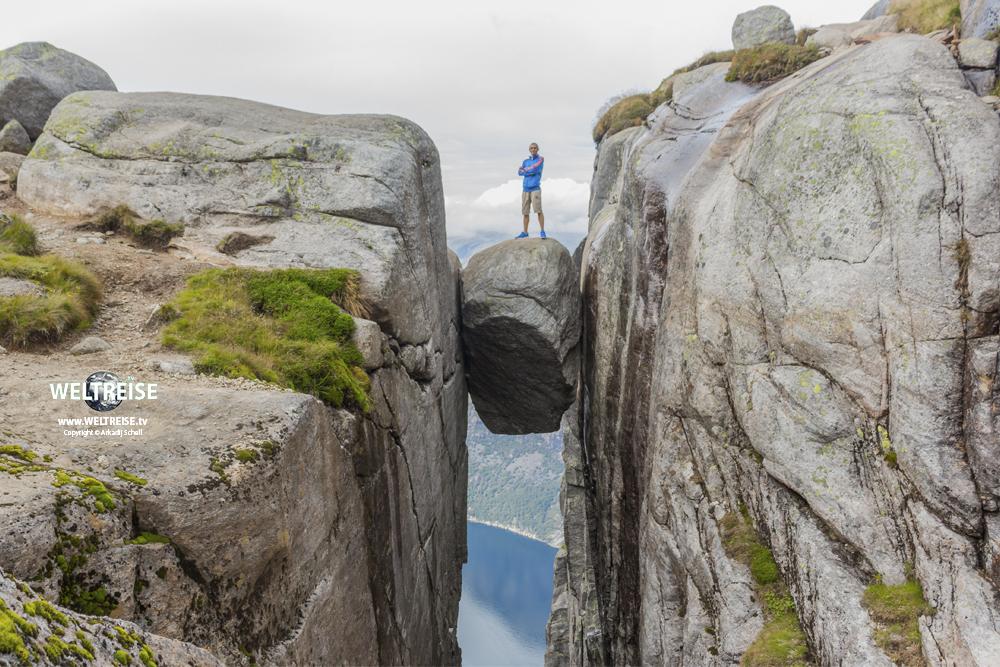 WELTREISE in Norwegen. Arkadij auf dem Kjeragbolten in Rogaland.