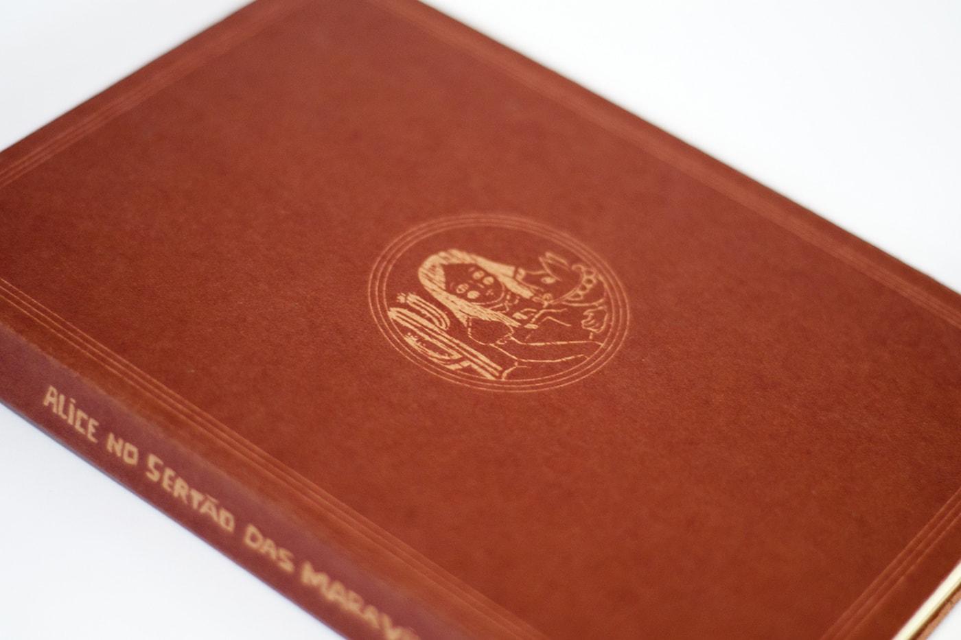 Foto da capa do projeto impresso - ela é marrom com impressão da personagem Alice em detalhes em dourado.