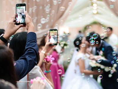 Novios besándose en una nube de burbujas e invitados con los móviles en alto fotografiando el momento
