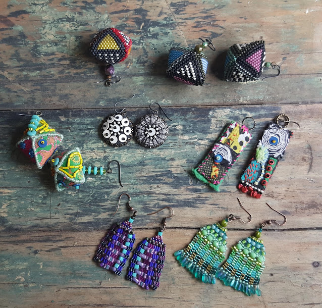 a collection of earrings I made in front of TV in May 2020. Some beaded, some cloth