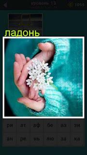 женская ладонь на которой находятся мелкие цветочки белого цвета