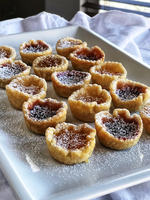little cups of pastry filled with jam and sprinkled with powdered sugar