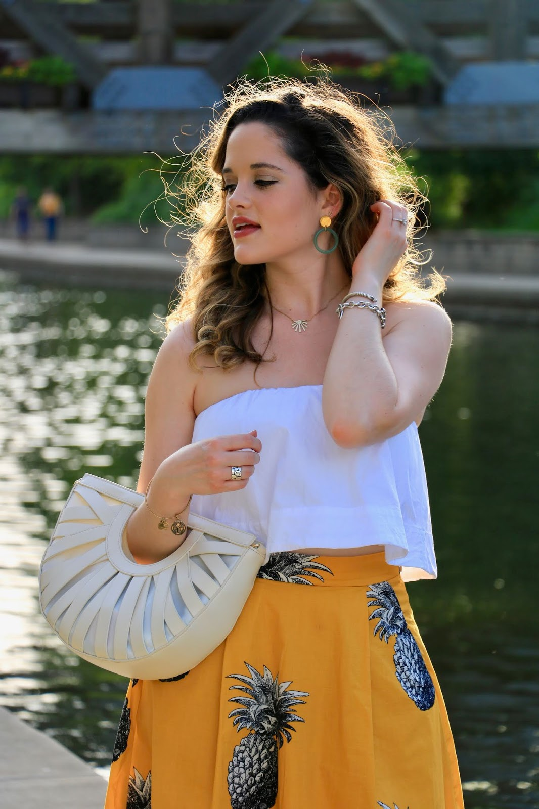 Nyc fashion blogger Kathleen Harper wearing a pineapple midi skirt with a strapless, white crop top.