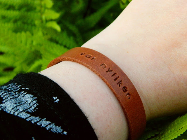A brown leather bracelet made by Stina Glaas worn on a wrist