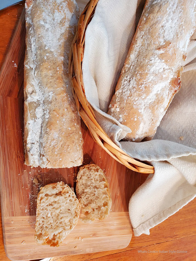 this is two loaves of no knead bread in a bread basket on a wooden board sliced