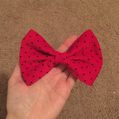 A picture of a finished hair bow, made of red polka dot fabric