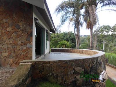 Banco de pedra em cima do muro de pedra com o assento de cimento queimado em sacada de sala de estar de residência em Atibaia-SP.