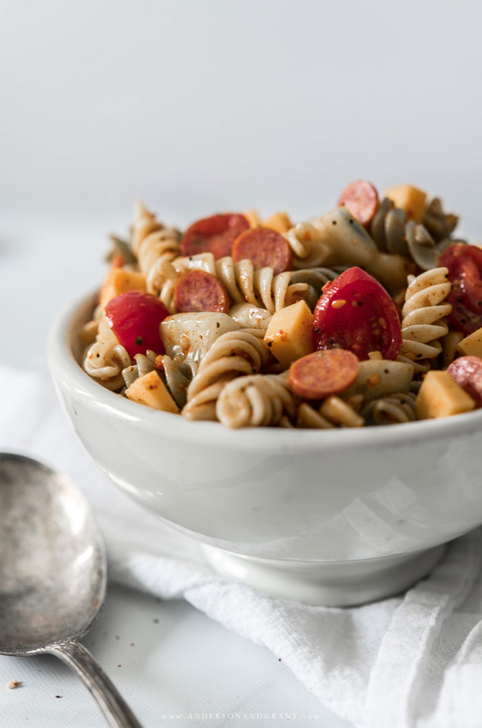 White bowl filled with Pasta Salad with tomatoes and pepperoni