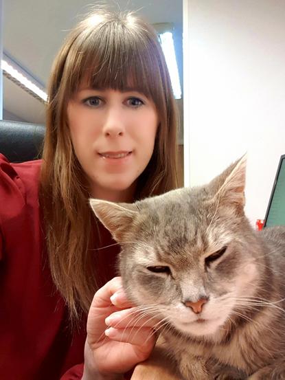 brunette woman stroking grey tabby cat