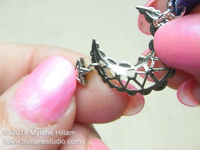 Hooking the loop of the star bead through the filigree of the moon charm
