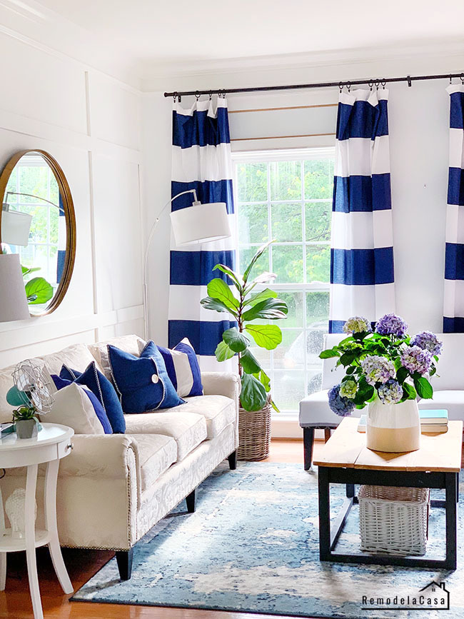 living room with striped navy and white drapes, round mirror, blue rug and blue accents.