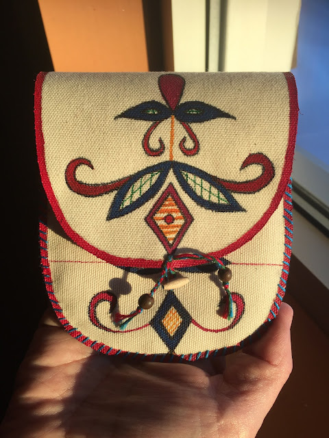This is a small purse made by Trifona Simard. She decided to paint on canvas, as she wanted to explore her talent before committing to painting on caribou-skin. Before she painted on the canvas, she practiced painting designs on paper until she gained confidence in handling the paint and the tools.