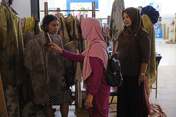 Pengunjung berminat melihat berbagai kain yang dipajang