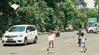 bermain layang layang di jalan