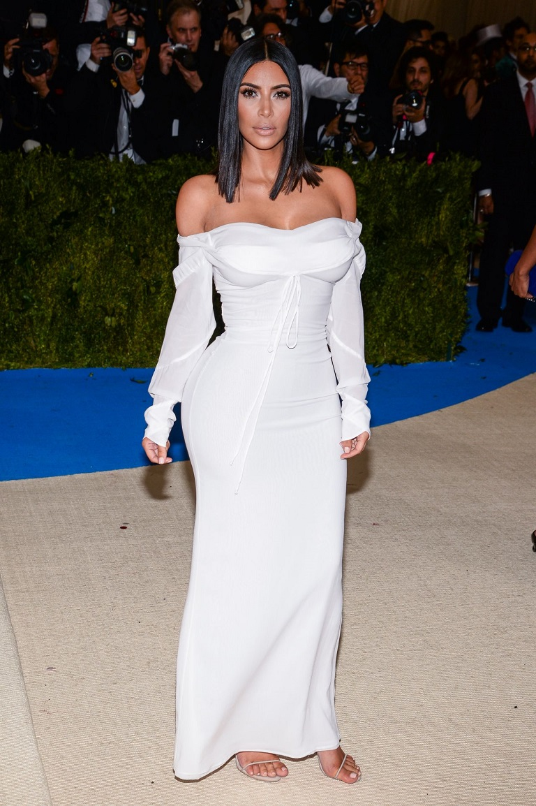 Kim Kardashian arrived at the Met Gala on Monday in an off-the-shoulder white Vivienne Westwood dress and simple sandals