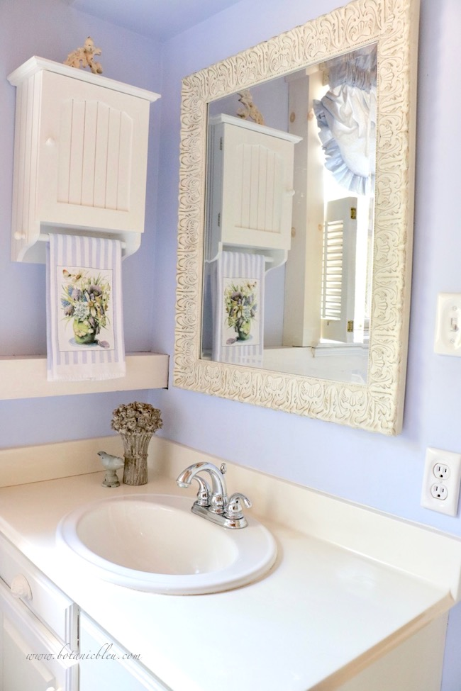 small vanity in master bathroom with a new white wood carved mirror