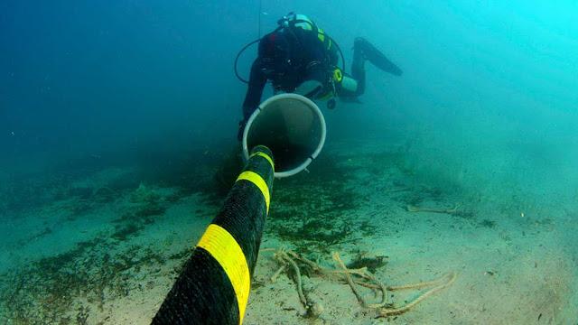 Mergulhador checando cabo de fibra ótica no fundo do mar