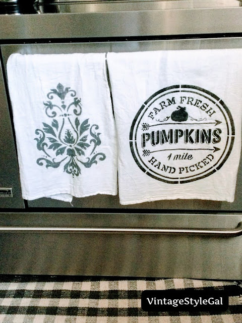 2 custom towels hanging side by side on bar on oven door