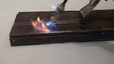 بشبوري لهب يخرج منه نار موجه على قطعة من الخشب