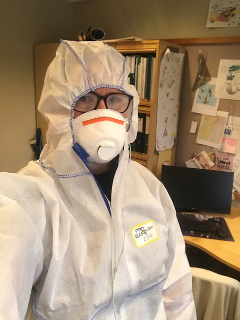 Suojahaalariin ja -maskiin pukeutunut henkilö, takana toimisto