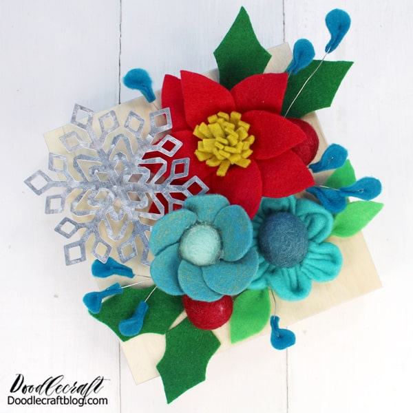 Now arrange the flowers on the wood canvas. Add some leaves and some holly berries. Then hot glue everything in place. Cut a felt ball in half to glue the snowflake on the board and give it some lift.