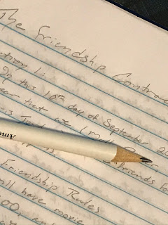 Close-up of a notebook page with words written in pencil, and the pencil sits across the page, obscuring many of the words.