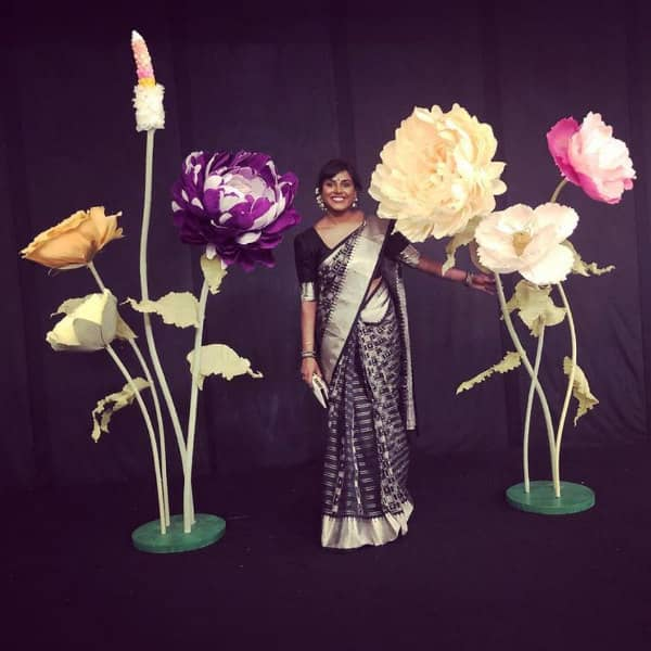 gigantic paper flowers stand on circular bases alongside woman