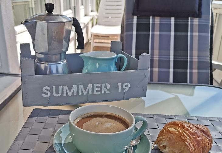 Frühstückstisch mit Obstkistentablett und Kaffeetasse