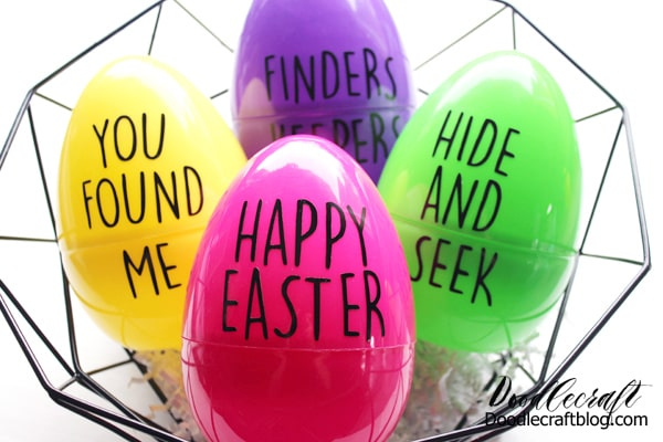 Wire basket with 4 giant plastic eggs in purple, green, yellow and pink with black vinyl phrases in Rae Dunn inspired fonts for easter egg hunt.