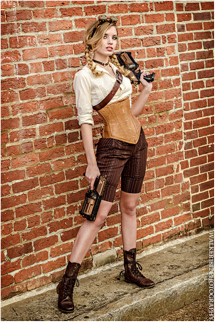 Women's steampunk clothing: shorts, corset, blouse, boots, goggles holding guns in front of a brick wall.