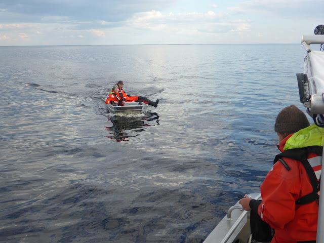 Kaksi henkeä pelastautumispuvuissa pienessä veneessä tulossa kohti isoa venettä