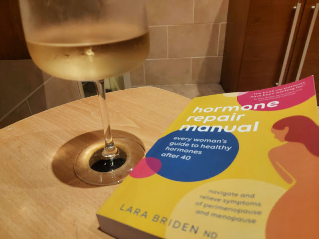 A glass of white wine and a book rest on a wooden laundry basket lid