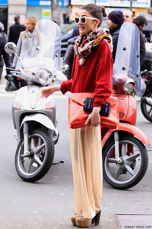 Woman in the streets of Milan wearing seethrough pants with high heels. Street style fashion outfit.