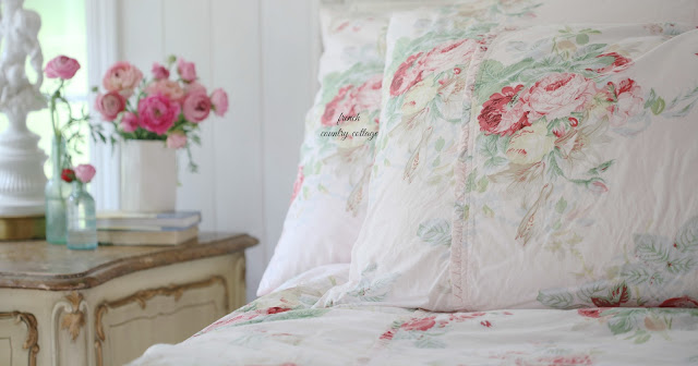 flower blush bedding on bed with flowers on nightstand