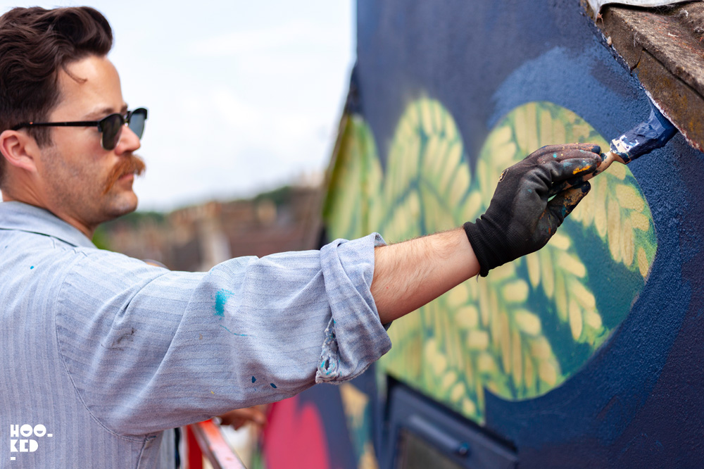 Close up detail of Beau Stanton painting a mural in Walthamstow, London