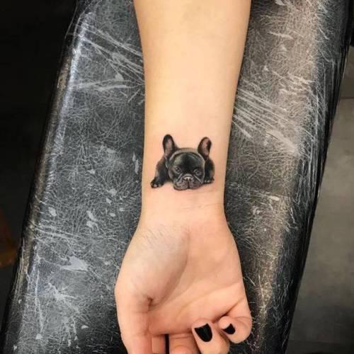 foto de un tatuaje pequeño de bulldog frances en la muñeca de una chica