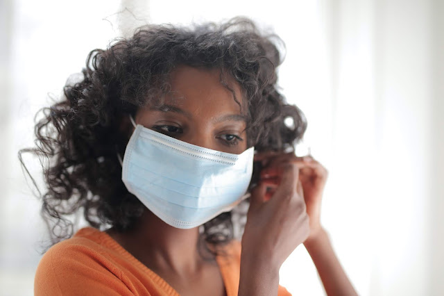 A lady putting on a surgical face mask.