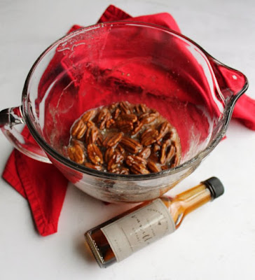glass bowl filled with sugar syrup and pecans with bottle of homemade vanilla extract
