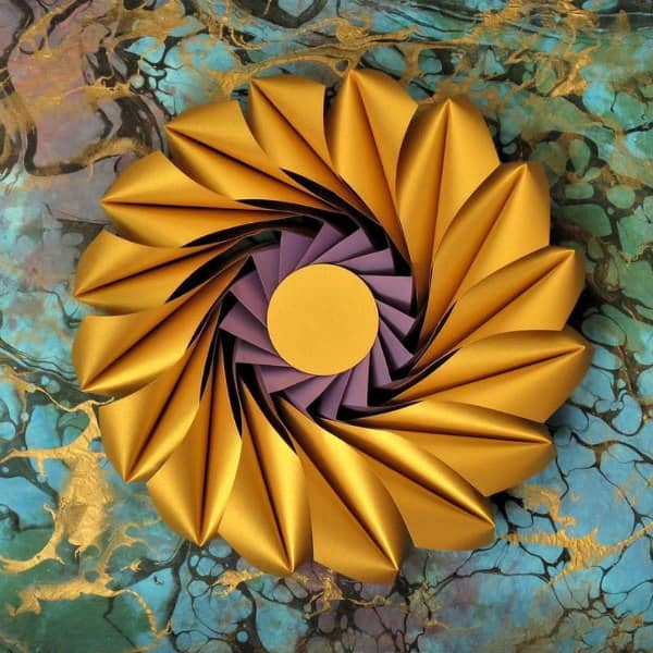 circular 3D paper sculpture in gold and purple on handmade paper background