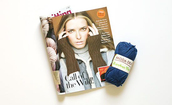 Vogue Knitting magazine opened to mitt pattern page and a skein of blue Moda Dea Bamboo Wool on a white background.