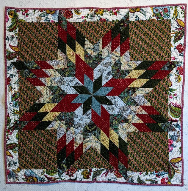 An old-fashioned quilt of cotton prints in light and dark blue, red, pale yellow, and white sits on a reproduction print of small fuchsia flowers on mustard. The border is a large-scale Jacobean floral on white and the binding is pink stripe homespun.