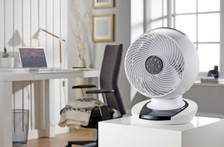 A white desktop fan sitting in an office showing a computer behind