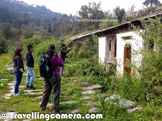 Hope you have enjoyed the journey of first two days with us so far. If you haven't gotten a chance, we recommend to check out Part-1 & Part-2 of the journey and then come back here to enjoy the third day trek to Dhanachuli Village around Kumaun hills. Let's start this Photo Journey to the beautiful Dhanachuli Village.It was bright sunny morning at Dhanachuli and some of us were up at 6:30am. Unpredictable weather during last two days had created so much curiosity that everyone was excited to see bright morning on third day. It opened the gates for the trek to the abandoned village of Dhanachuli. We started from Te Aroha at around 7:00 am. We drove from Te Aroha to the market of Dhanachuli village. We stopped near Bank of Baroda and started our trek downwards through green farms facing snow covered peaks. Mr. Sumant Batra personally led the entire trek and kept us informed about various trees, crops, plants, architecture & people.For initial 20 minutes, we were walking through the habitat area which is comparatively close to the main road which connects Dhanachuli village to other parts of Kumaun. Most of the villagers have pets and mainly cows & goats. Corn crops were all over the farms and some of the farms also had seasonal vegetables - peas, cabbage, bringle, tomatoas, green chillies, kidney-beans (Rajmah) etc. Dhanchuli village is deep in the valley surrounded by snow capped hills on one side and steep green mountains on other side. Dhanachuli hills are probably some of the highest hills in Kumaun region.At the end of the trek were some dilapidated houses of the old Dhanachuli village. Most of the old village is abandoned with only a couple of houses still occupied. The villagers, it seems, have moved to houses closer to the road.The houses were adorned with some interesting carvings and designs. Sumant pointed out some samples of carvings from as far as Rajasthan. He expressed his amazement at finding such designs up here in Uttarakhand. One possible explanatio