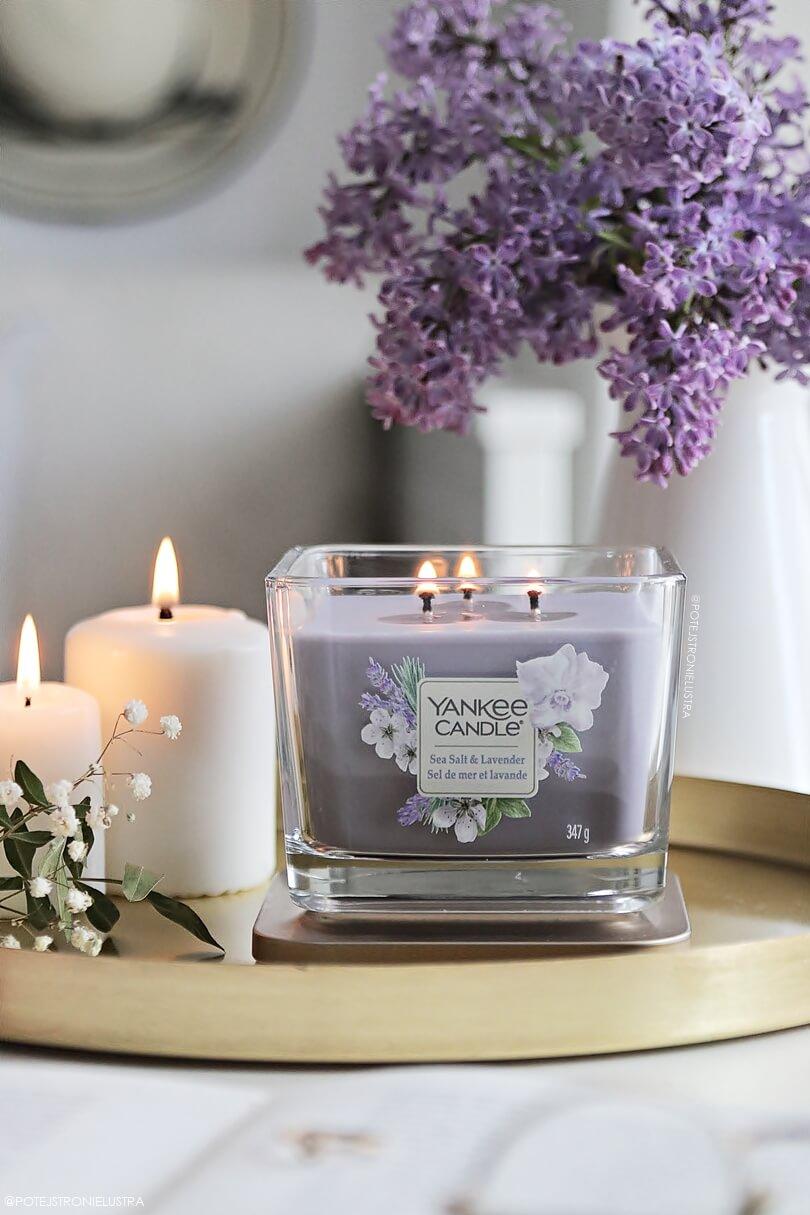 świeca yankee candle sea salt & lavender na tle ładnego jasnego pokoju i bukietu kwiatów