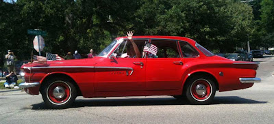 Red Dodge Lancer with a small American flag waving out the window