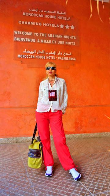 Изображение туристки на фоне таблички отеля