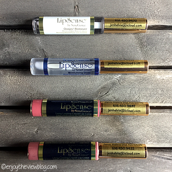 Four tubes of LipSense Lip Color by SeneGence lying on a wooden table