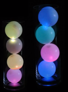 Vier beleuchtete Luftballons in einer Glassäule als Tischdekoration.