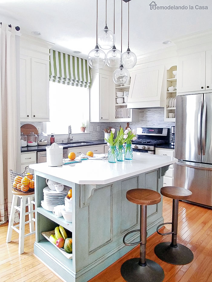 White kitchen with light blue island, oranges on counter and green roman shade