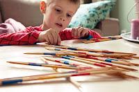 Renkli şeritli çubuklarla mikado oynayan bir çocuk